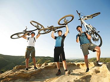 USA, California, Laguna Beach, Mountain bikers on top of hill holding up their bikes
