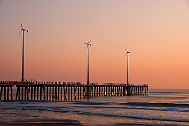 USA, North Carolina, Outer Banks, Kill Devil Hills, pier with wind turbines at sunset
