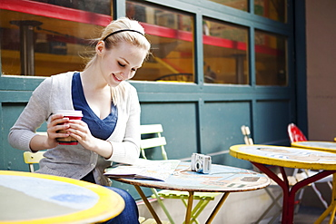USA, Seattle, Young woman sitting with coffee and reading map