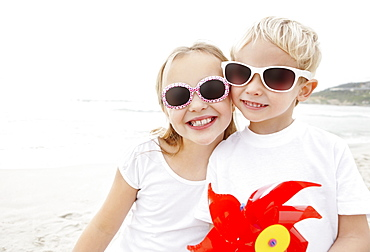 Portrait of brother (4-5) and sister (10-11) wearing sunglasses on beach