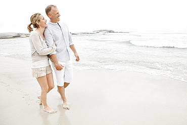 Couple holding hands and walking on empty beach