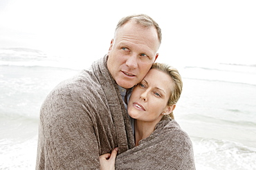Embraced couple covered by blanket looking away on beach