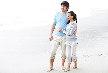 Couple walking barefoot on the beach