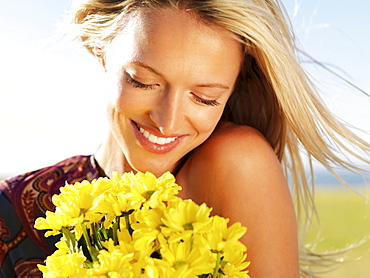 Blond woman holding yellow flowers
