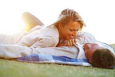 Couple lying down on picnic blanket