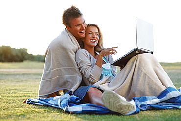 Couple looking at laptop outdoors