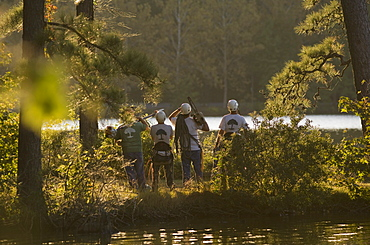 Four construction workers by a lake with tools