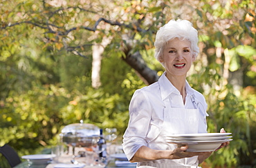 Senior woman standing in garden holding stack of plates