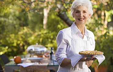Senior woman standing in garden holding plate with pie
