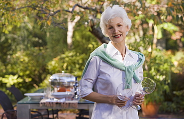Senior woman standing in garden holding wineglasses