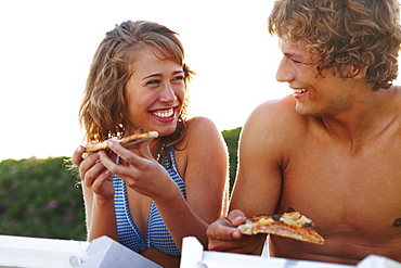 Young couple eating pizza at beach