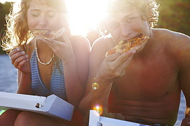 Young couple eating pizza on beach