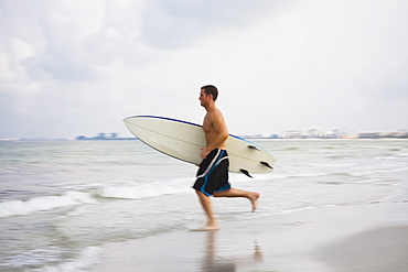 Man carrying surfboard into water