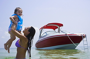 Mother holding up daughter in water, Florida, United States