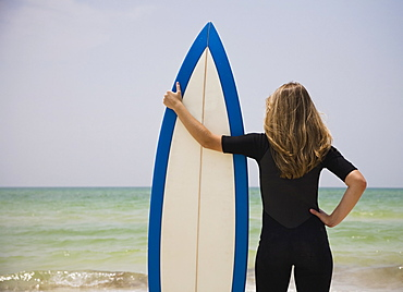 Girl holding surfboard, Florida, United States