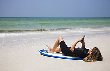 Girl looking at cell phone on surfboard, Florida, United States