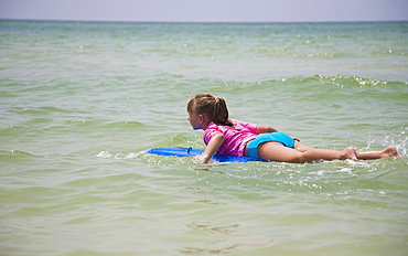 Young girl floating on boogie board, Florida, United States