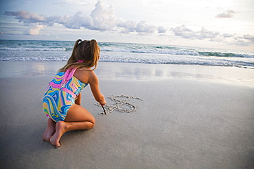 Girl drawing dollar sign in sand, Florida, United States