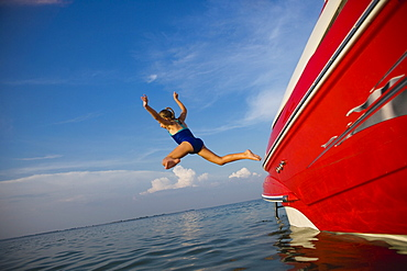 Young girl jumping off boat, Florida, United States