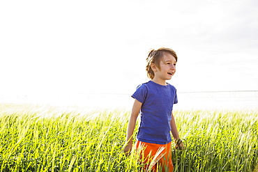 Boy (4-5) standing in grass and looking away, Colorado, USA