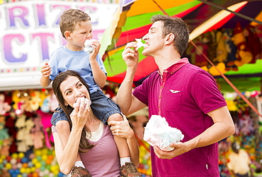 Happy family with son (4-5) in amusement park eating cotton candy, USA, Utah, Salt Lake City