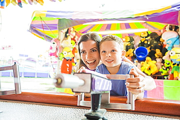 Mother and son (4-5) playing with water gun in amusement park, USA, Utah, Salt Lake City