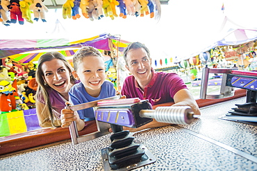 Happy Family with son (4-5) playing with water gun in amusement park, USA, Utah, Salt Lake City