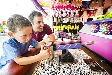 Father with son (4-5) playing with water gun in amusement park, USA, Utah, Salt Lake City
