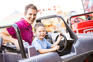Father with son (4-5) driving toy car in amusement park, USA, Utah, Salt Lake City