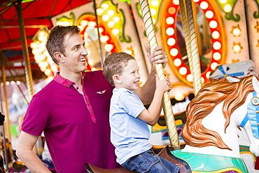 Father and son (4-5) on carousel in amusement park, USA, Utah, Salt Lake City