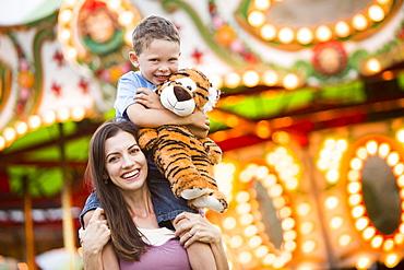 Mother giving her son (4-5) piggyback ride in amusement park, USA, Utah, Salt Lake City