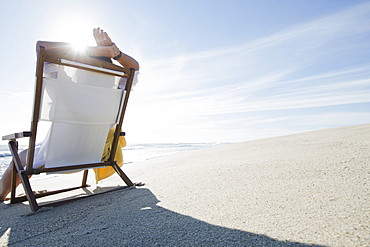 Rear view of woman relaxing on chair at beach, USA, Massachusetts, Nantucket