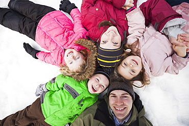 Directly above portrait of three children (2-3, 4-5) with parents lying on snow