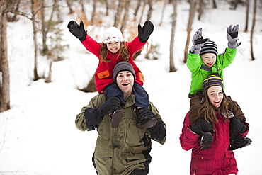 Portrait of parents carrying children (2-3, 4-5) on shoulders, USA, Utah, Highland