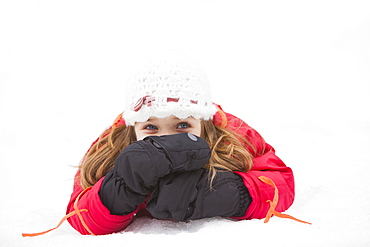 Portrait of girl (2-3) lying on snow
