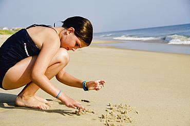 Girl (8-9) playing at beach, Nags Head, North Carolina