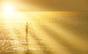 Man standing on paddle board at sunset