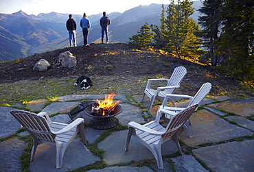 Three people standing near fire pit looking at landscape, Colorado, United States