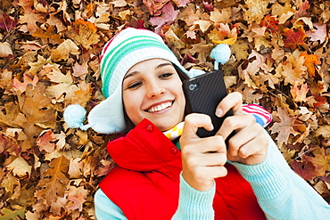 Young woman lying on autumn leaves and using