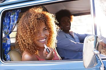Smiling woman applying lipstick in van, man in background