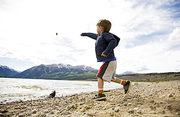 Boy (2-3) throwing rock in lake, Colorado, USA