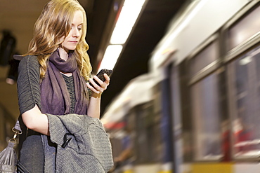 USA, California, Los Angeles, Woman sending text messages on subway station
