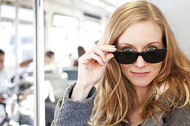Portrait of woman wearing sunglasses in subway train