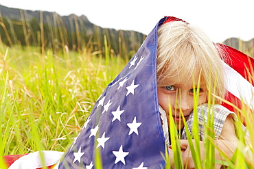 Portrait of boy (6-7) wrapped in American flag