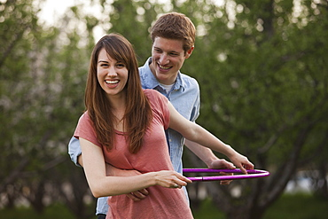 Young couple using plastic hoop in orchard