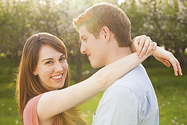 Young couple embracing in orchard