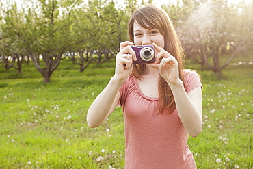 USA, Utah, Provo, Young woman holding digital camera in orchard