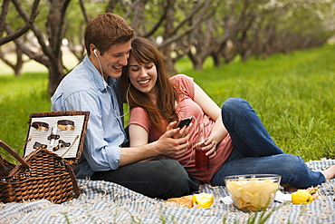 USA, Utah, Provo, Young couple with mp3 player in orchard