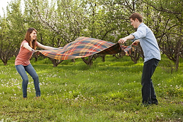 USA, Utah, Provo, Young couple holding blanket in orchard