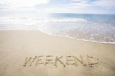 "USA, Massachusetts, Word ""weekend"" drawn on sandy beach"